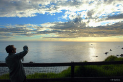 Person taking picture of ocean sunset at Esalen